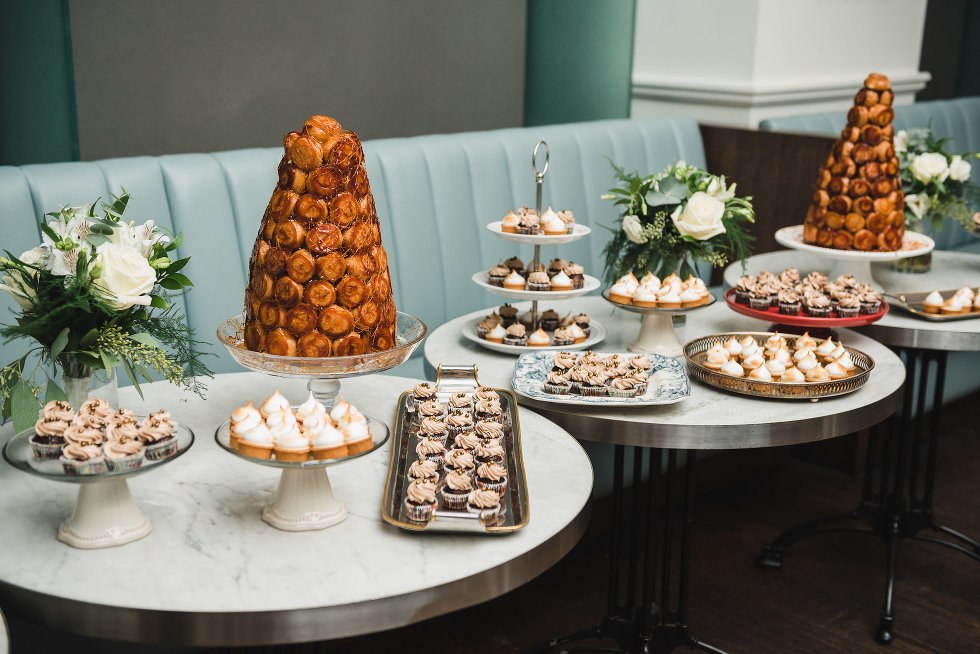 three tables covered with trays of pastries and white bouquets Toronto wedding photography