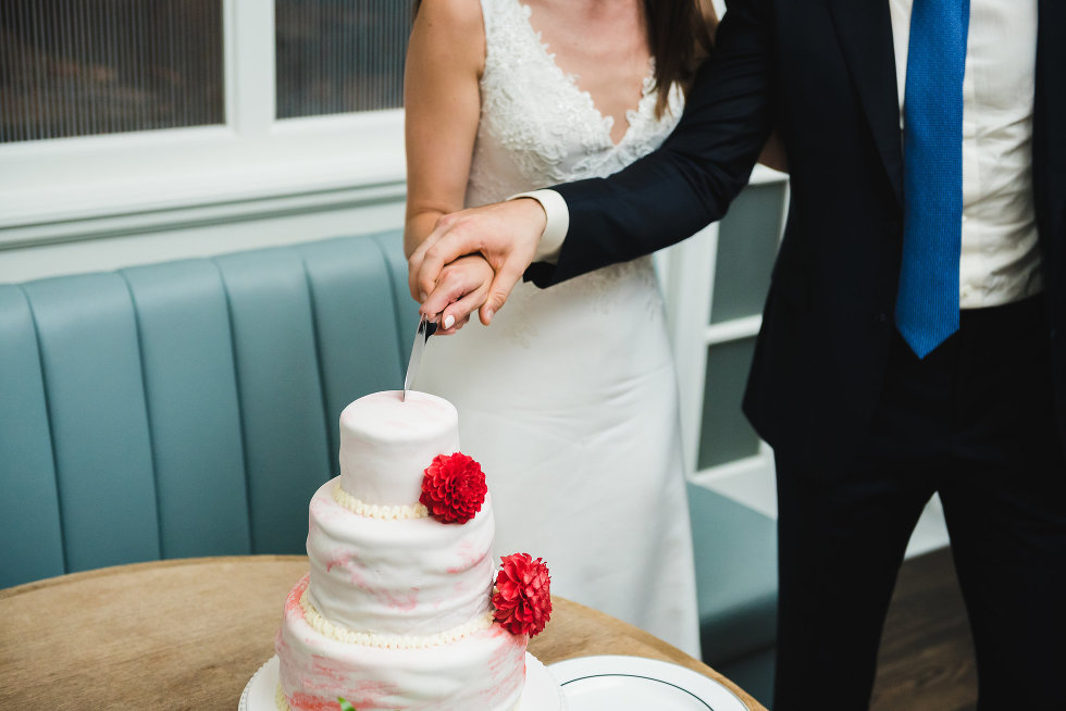 bride and groom holding knife and together cut a white wedding cake with red flowers on it Toronto wedding photography