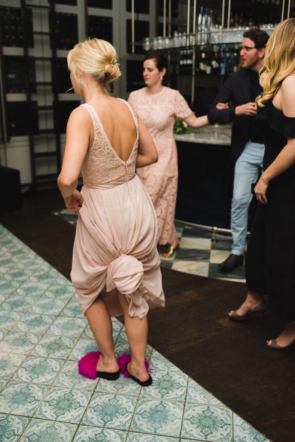 bridesmaid dancing in pink slippers on dance floor Toronto wedding photography