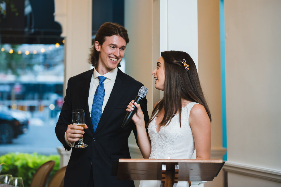 bride delivering speech into microphone at podium while groom stands next to her holding wine glass Toronto wedding photography Collette Grand Cafe