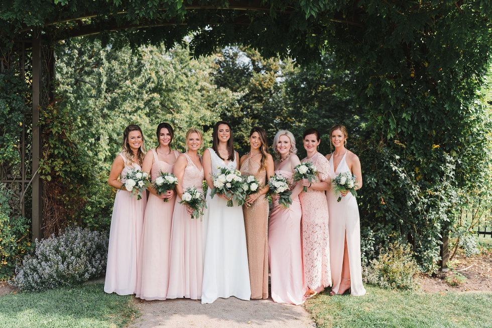 bride and her bridesmaids in a line holding bouquets Toronto wedding photography