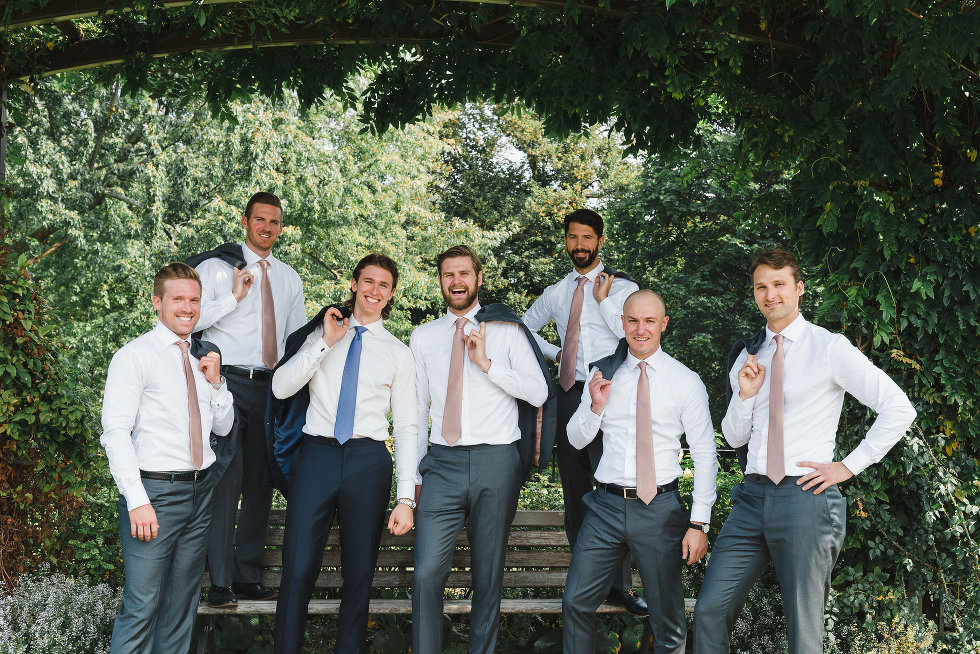 groom and his groomsmen with jackets draped over shoulders as they stand around park bench Toronto wedding photography