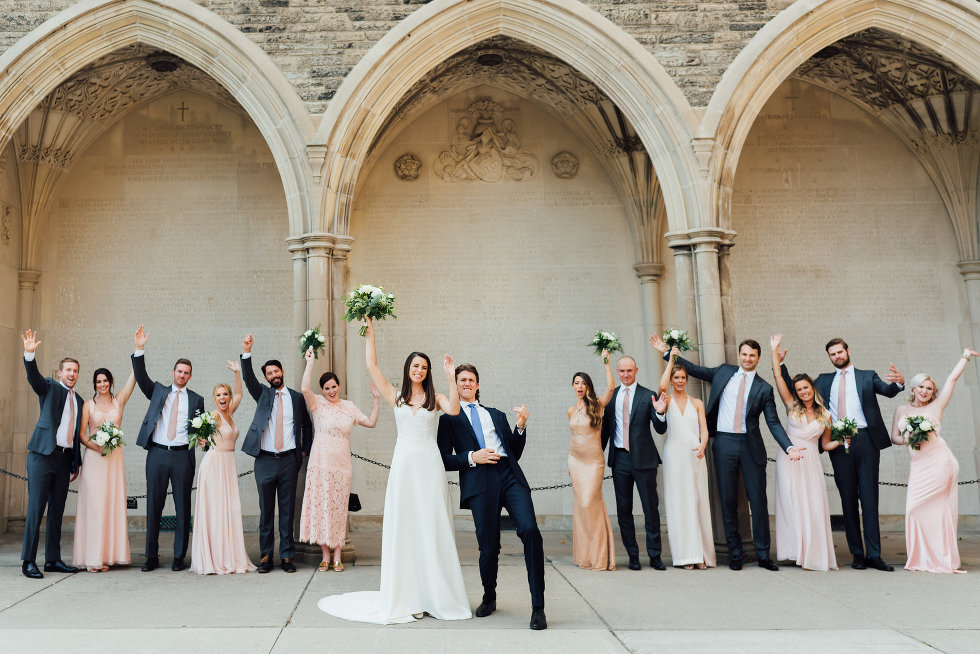 bride, groom, and wedding party with hands in the air in front of church arches Toronto wedding photography