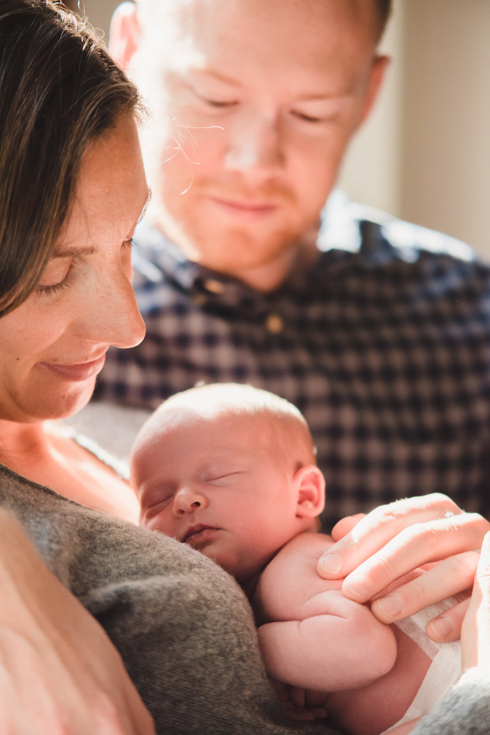 husband looks on as wife holds newborn to her chest Toronto lifestyle photographer Gillian Foster
