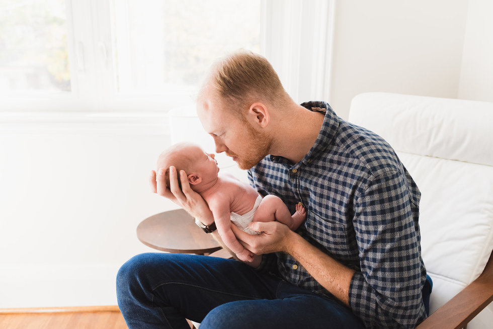man sitting in chair with his baby cradled in his hands Toronto lifestyle photographer