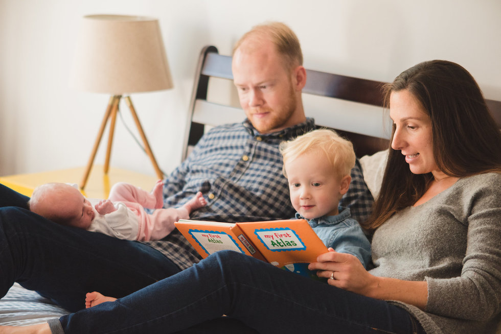 parents lying in bed with newborn and toddler while mother reads book to toddler Toronto lifestyle photographer