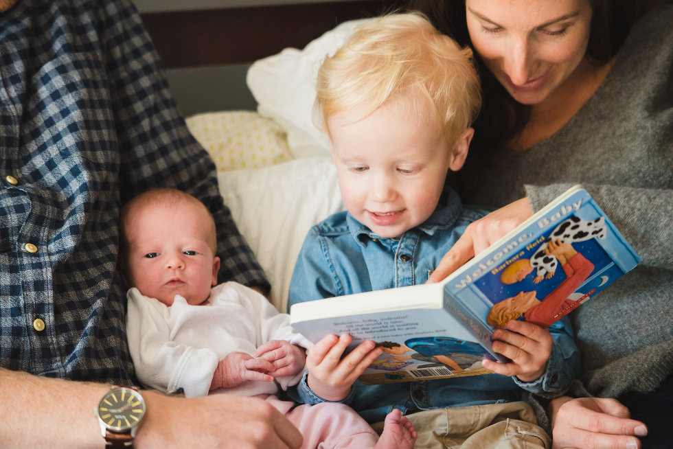 parents lying in bed with newborn and toddler while mother reads book to toddler Toronto