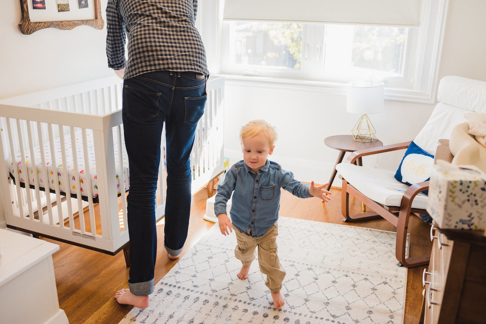 father lifting baby out of crib while toddler runs around room Toronto photographer