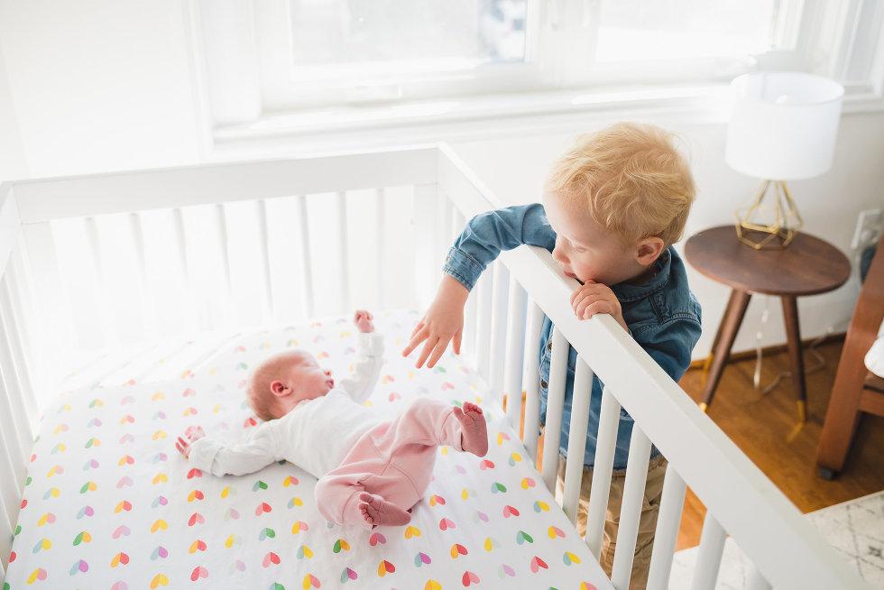 toddler reaches into white crib to touch baby sister Toronto