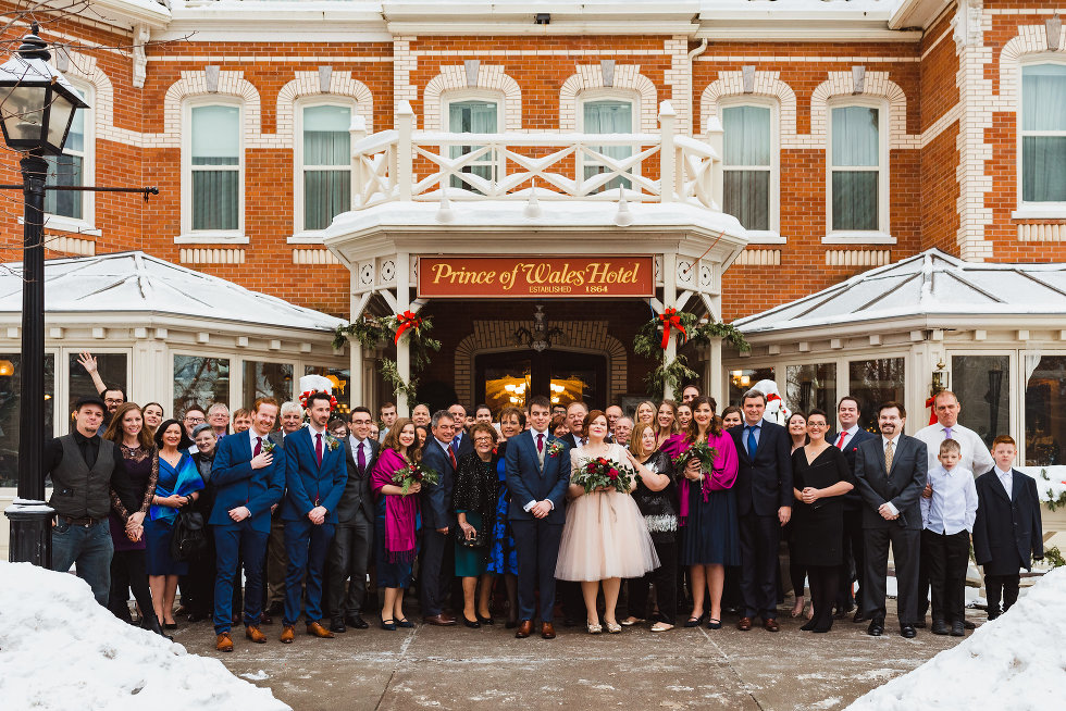 bride and groom surrounded by all their wedding guests out front of the Prince of Wales Hotel in Niagara