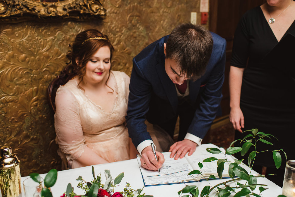 groom signs wedding certificate with bride watching Niagara wedding photography