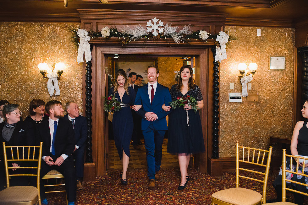 wedding guests watch as a groomsman and two bridesmaids enter Victorian room Prince of Wales Hotel Niagara wedding