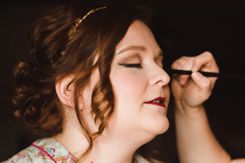 bride with eyes closed as her makeup artist applies eyeliner Toronto wedding