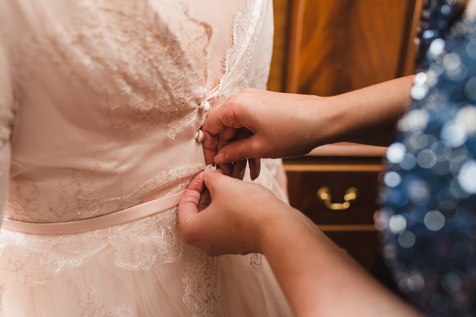 bride having her wedding dress buttoned up in the back Niagara wedding photography