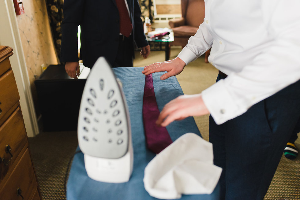 groom placing burgundy necktie on ironing board for ironing Niagara wedding