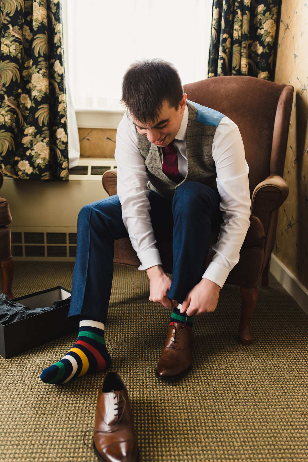 groom seated in chair tying up brown dress shoe with colourful striped socks Toronto wedding photography