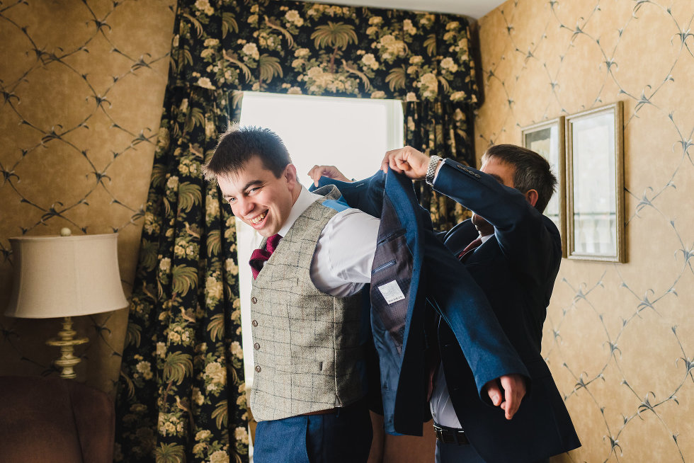 father of groom helping groom put on his blue suit jacket Niagara wedding photographer