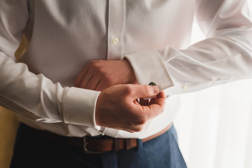 groom is attaching cufflinks to white shirt Toronto wedding photography
