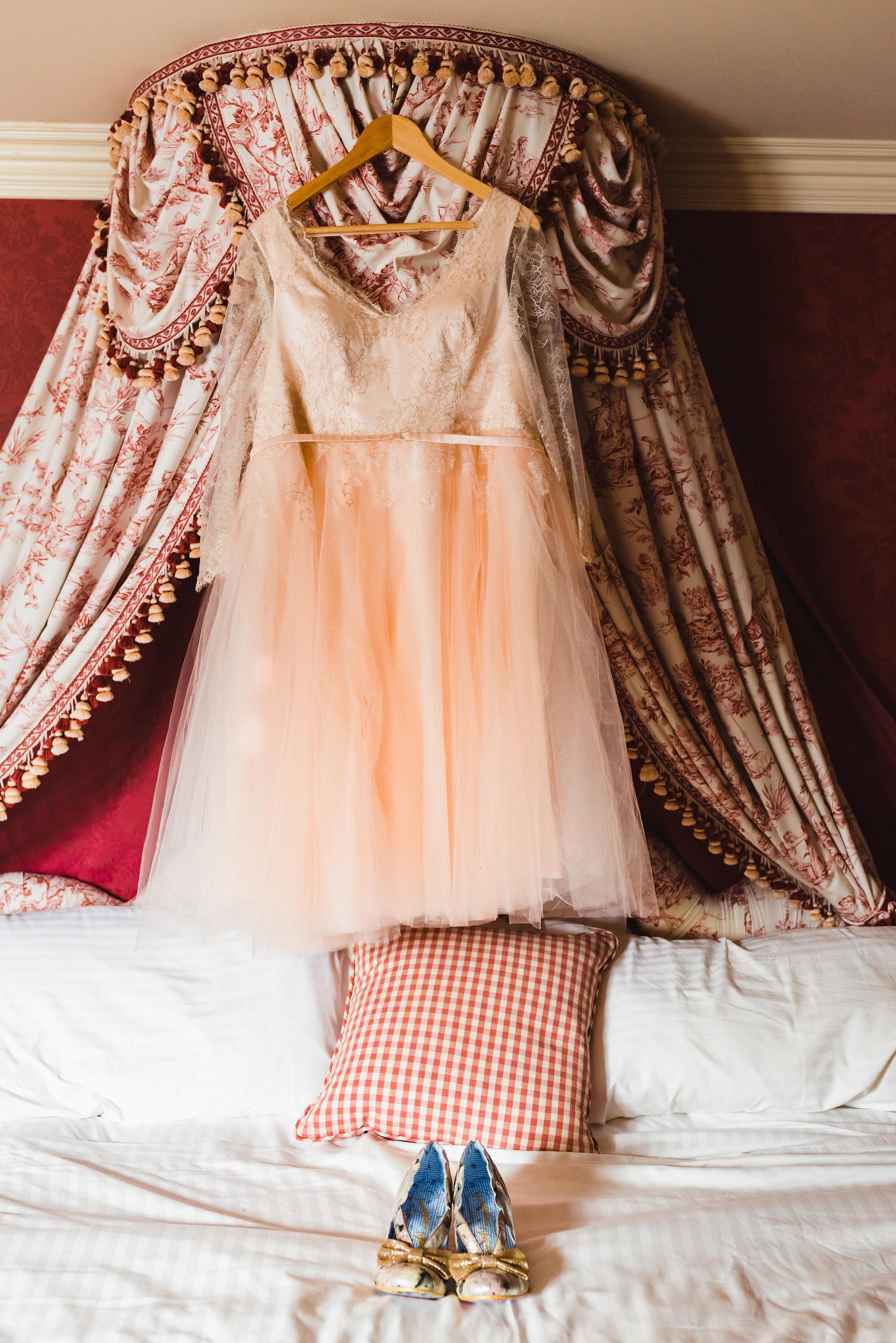 wedding dress hanging on headboard above white bed and wedding shoes Toronto Wedding photographer