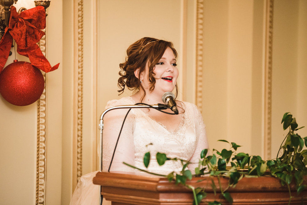 bride standing at podium delivering speech into microphone Niagara wedding photography