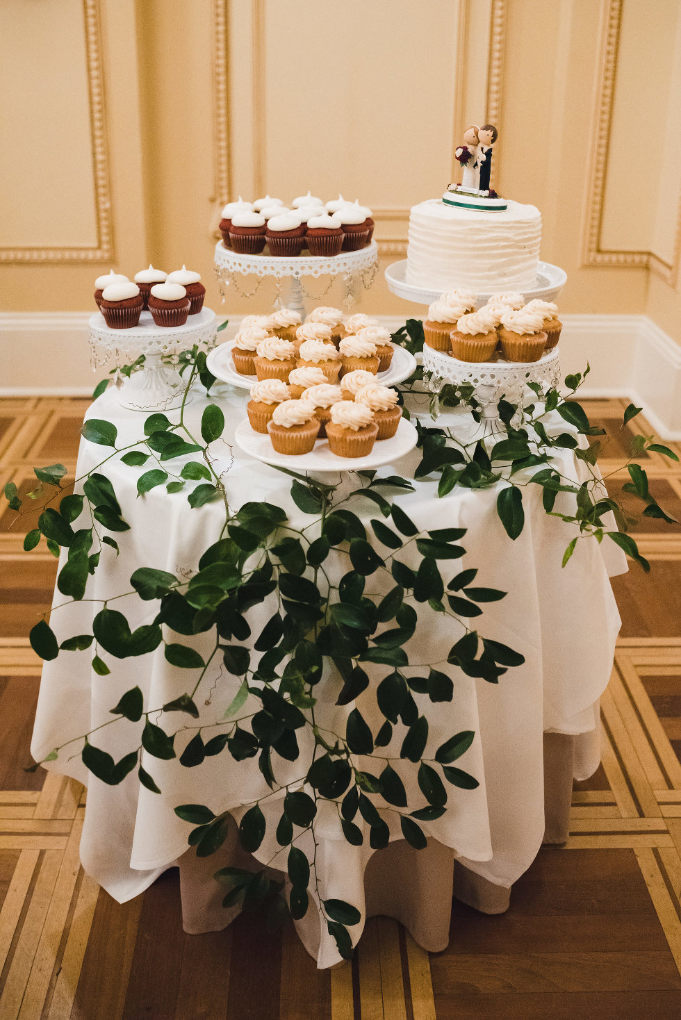 table with bride and groom topped wedding cake surrounded by cupcakes in Prince of Wales Hotel Niagara wedding photography