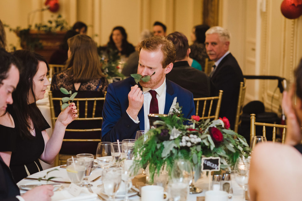 groomsman sitting down at table holds green leaves up to his lips to make a fake moustache Niagara wedding photography