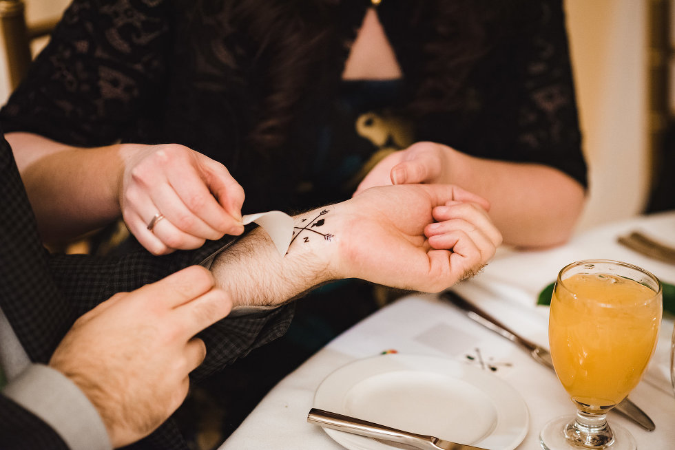wedding guests apply temporary tattoos at reception table in Prince of Wales Hotel Niagara wedding photography