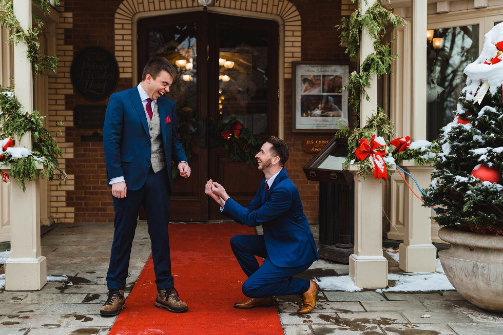 groomsman on one knee pretending to propose to a laughing groom Prince of Wales Hotel Niagara wedding photography Gillian Foster