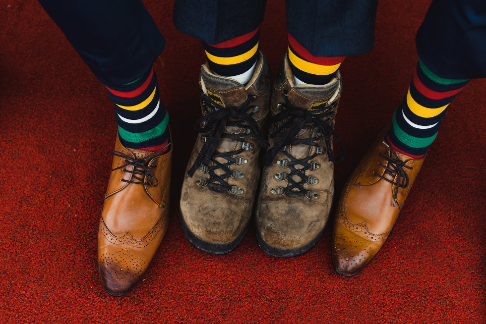 groomsmen showing off brown shoes and colourful striped socks over red carpet Toronto wedding photography