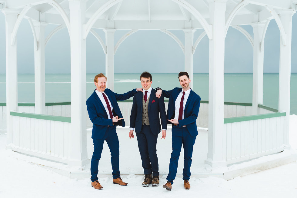 groom stands in front of white gazebo while groomsmen stand on either side of him and point at groom Niagara wedding photography