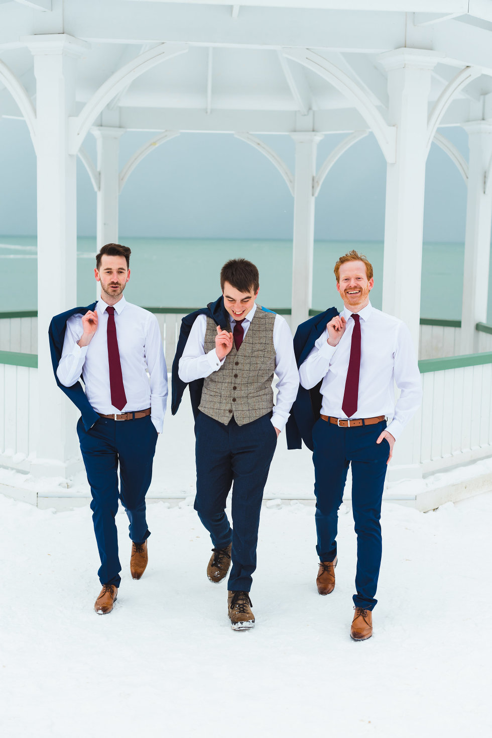 groom and his groomsmen walking away from white gazebo with their suit jackets hanging over their shoulders Prince of Wales Hotel Niagara wedding photography Gillian Foster