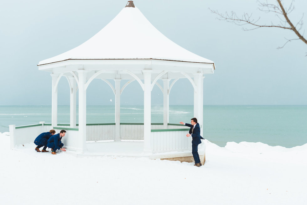 groom throwing snowball throw white gazebo at groomsmen hiding on other side Niagara wedding photography