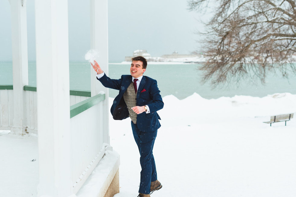 groom throwing snowball throw white gazebo Niagara wedding photography