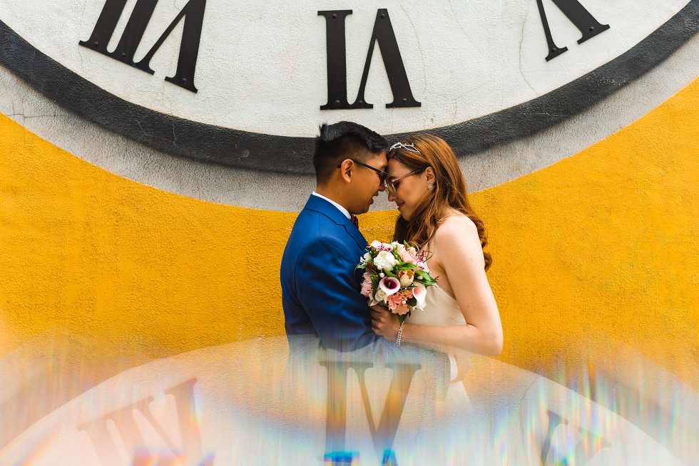 Bride and groom standing under a clock holding one another for their Toronto wedding photos