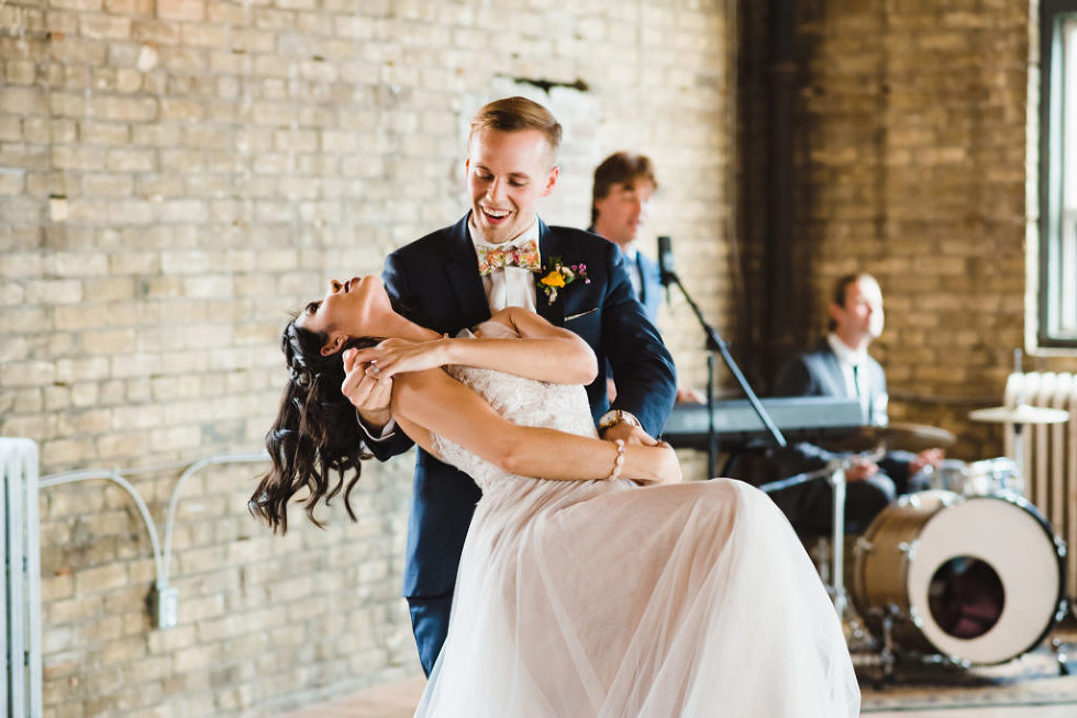 groom dipping bride as they dance in front wedding band at the Jam Factory Toronto wedding photography