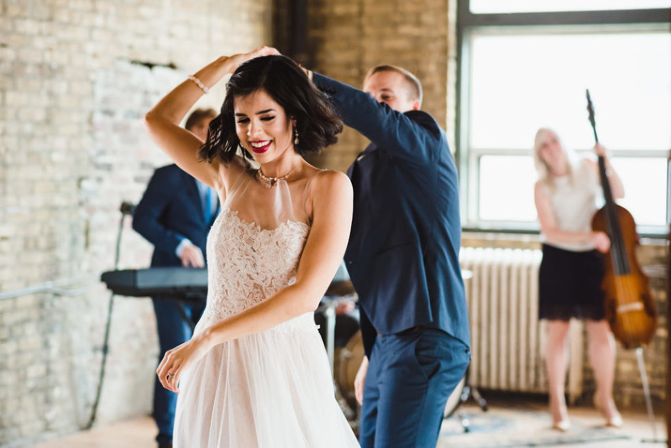 bride being twirled by her groom as they dance in front of their wedding band at the Jam Factory Toronto