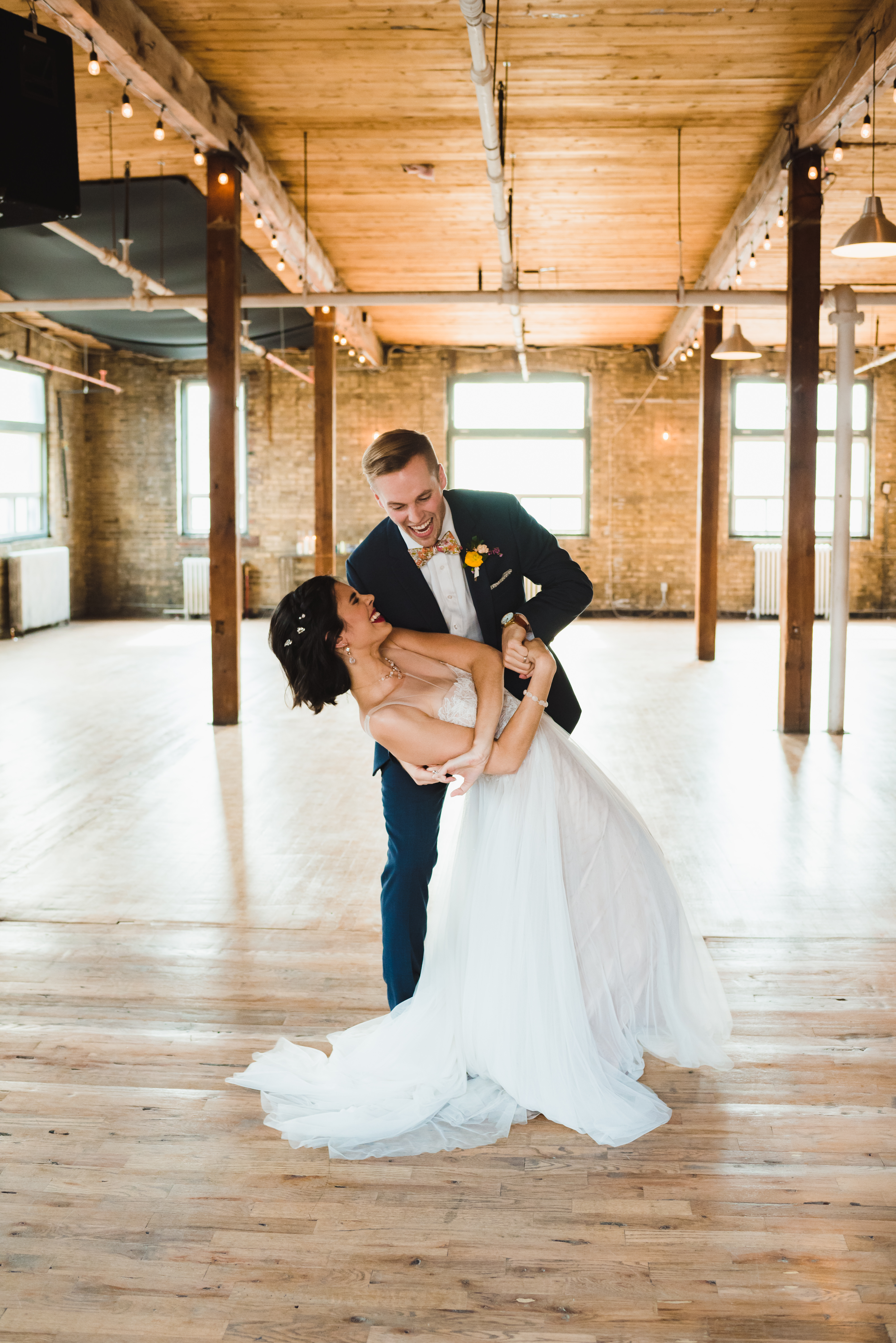 bride and groom laughing as groom dips his bride while dancing at the Jam Factory Toronto wedding photography
