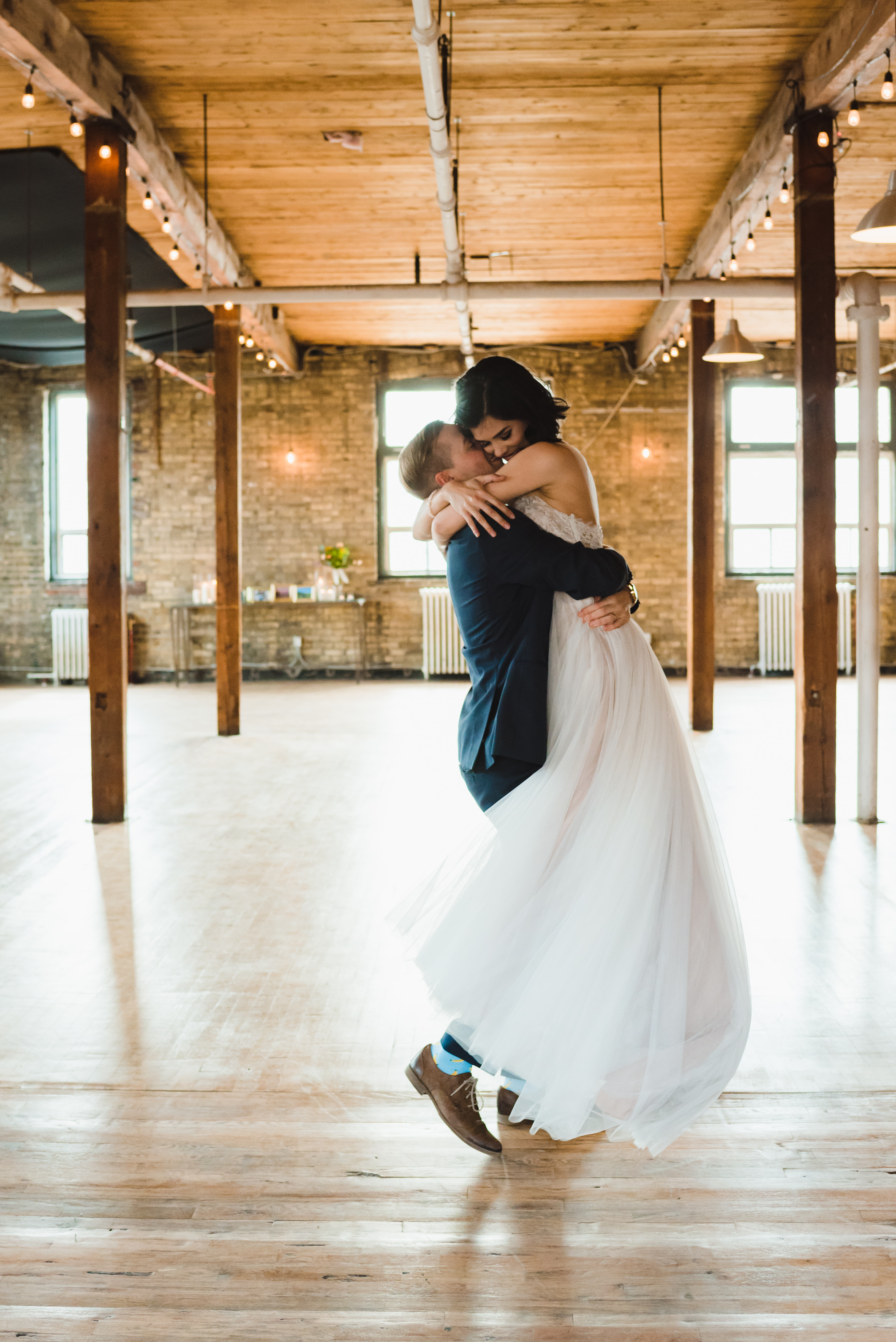groom lifting up his bride and hugging her at the Jam Factory Toronto wedding photography
