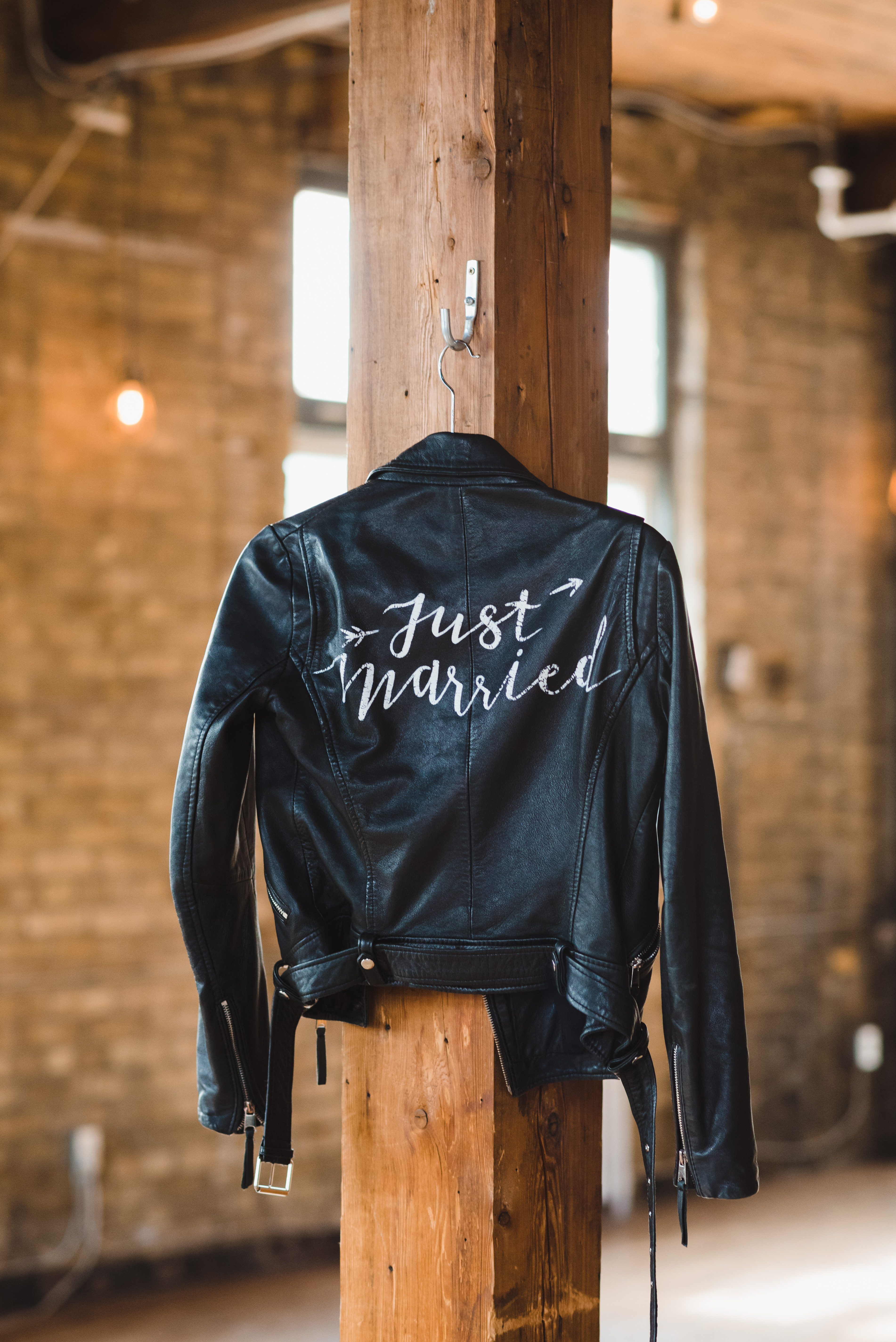 closeup of just married leather jacket hanging on wooden post at the Jam Factory Toronto wedding photography