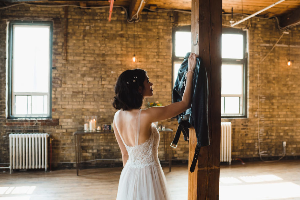bride reaching for her just married leather jacket hanging on wooden post at the Jam Factory Toronto wedding photography