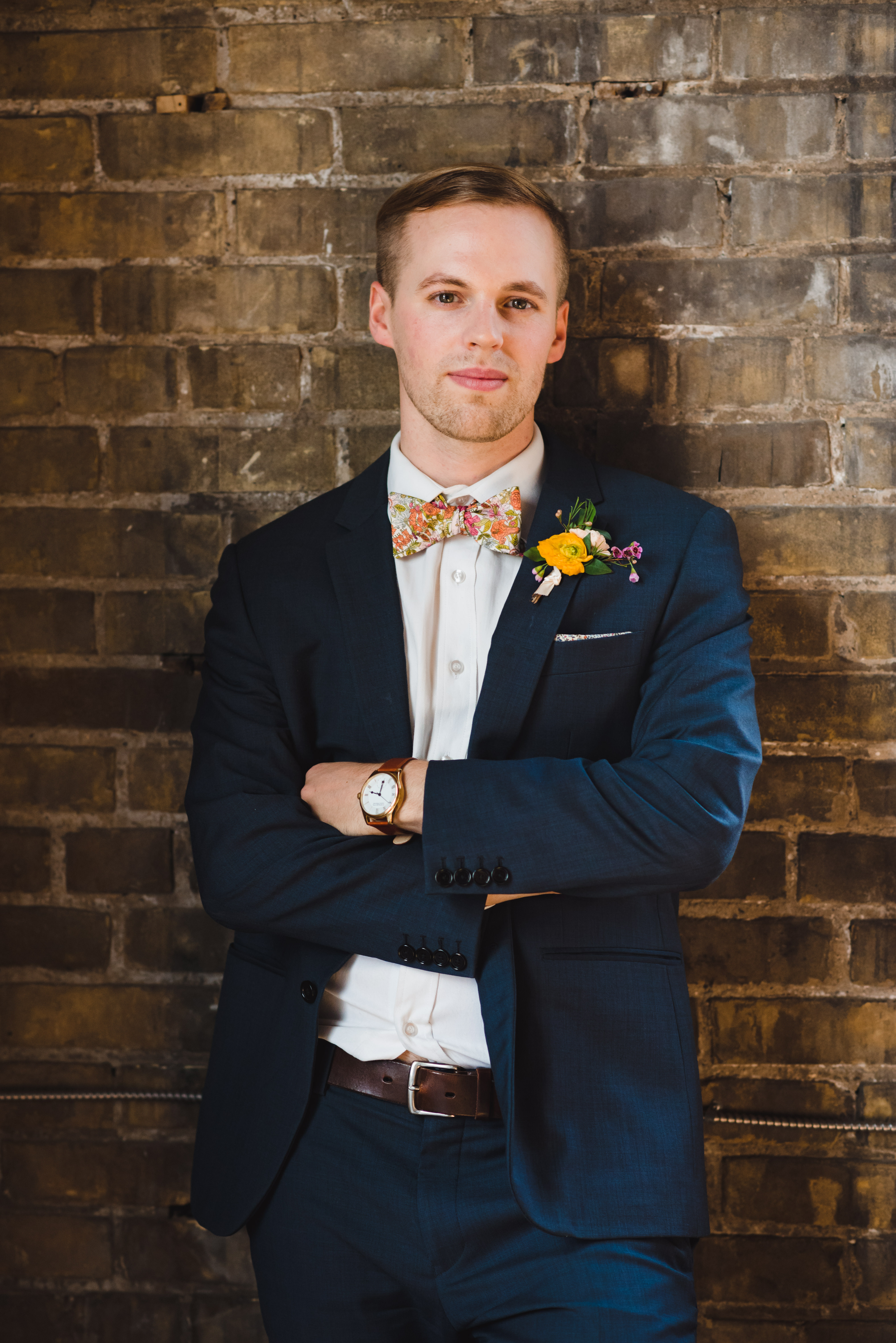 closeup of a groom wearing a blue suit with floral bowtie and boutonniere while leaning against old brick wall of the Jam Factory Toronto wedding photography