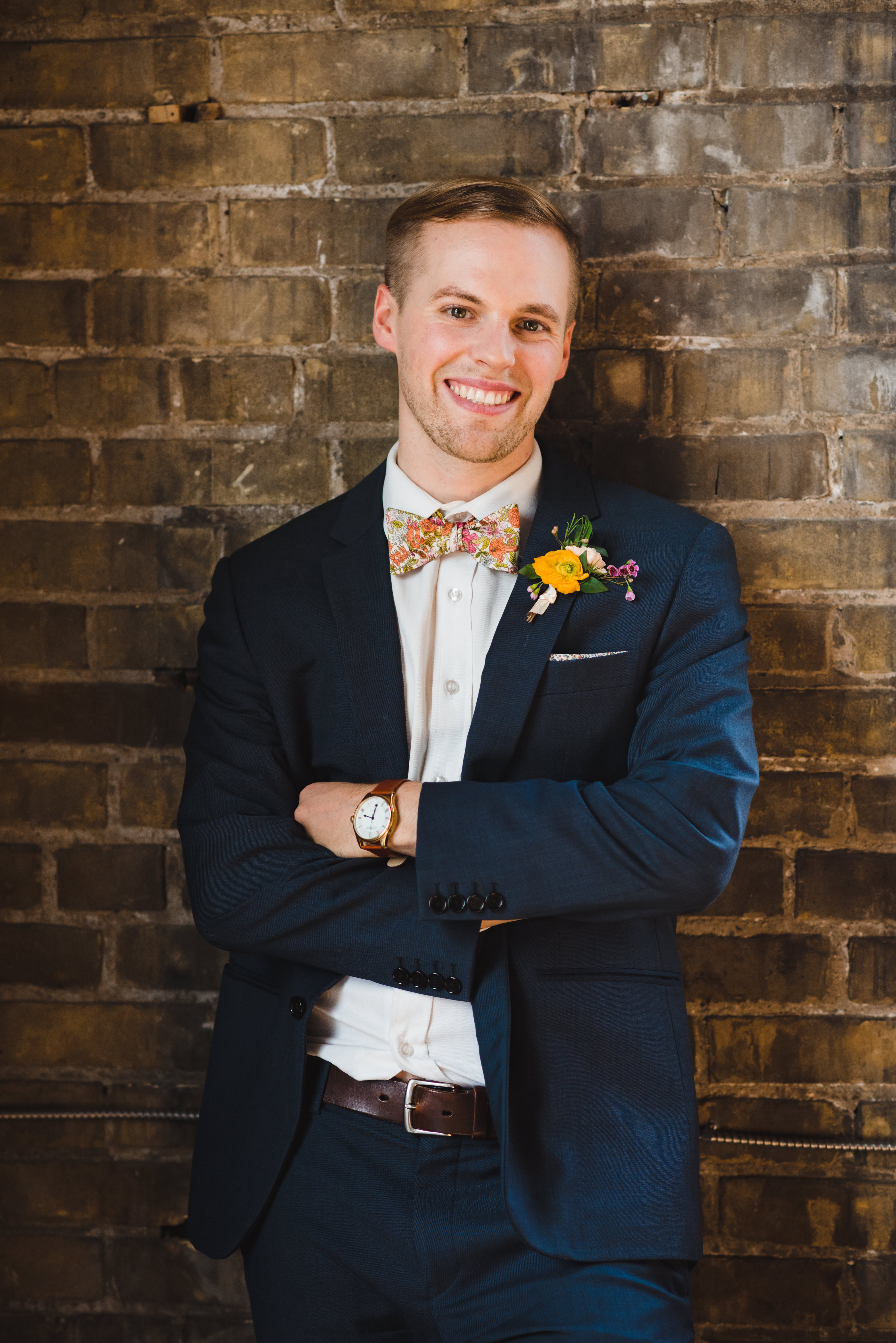 smiling groom wearing a blue suit with floral bowtie and boutonniere while leaning against old brick wall of the Jam Factory Toronto wedding photography