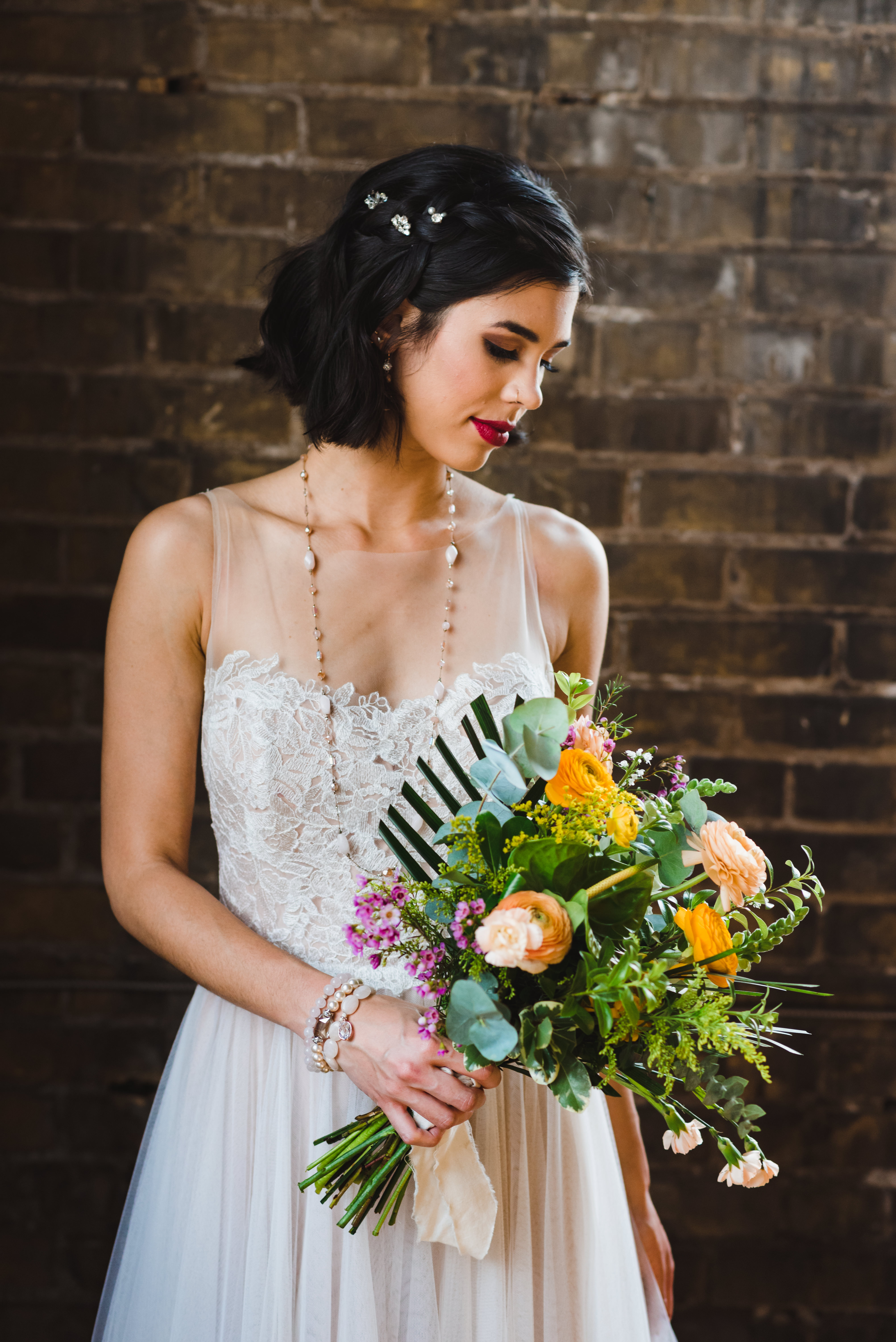 bride standing in front of old brick wall with bouquet at the Jam Factory Toronto wedding photography