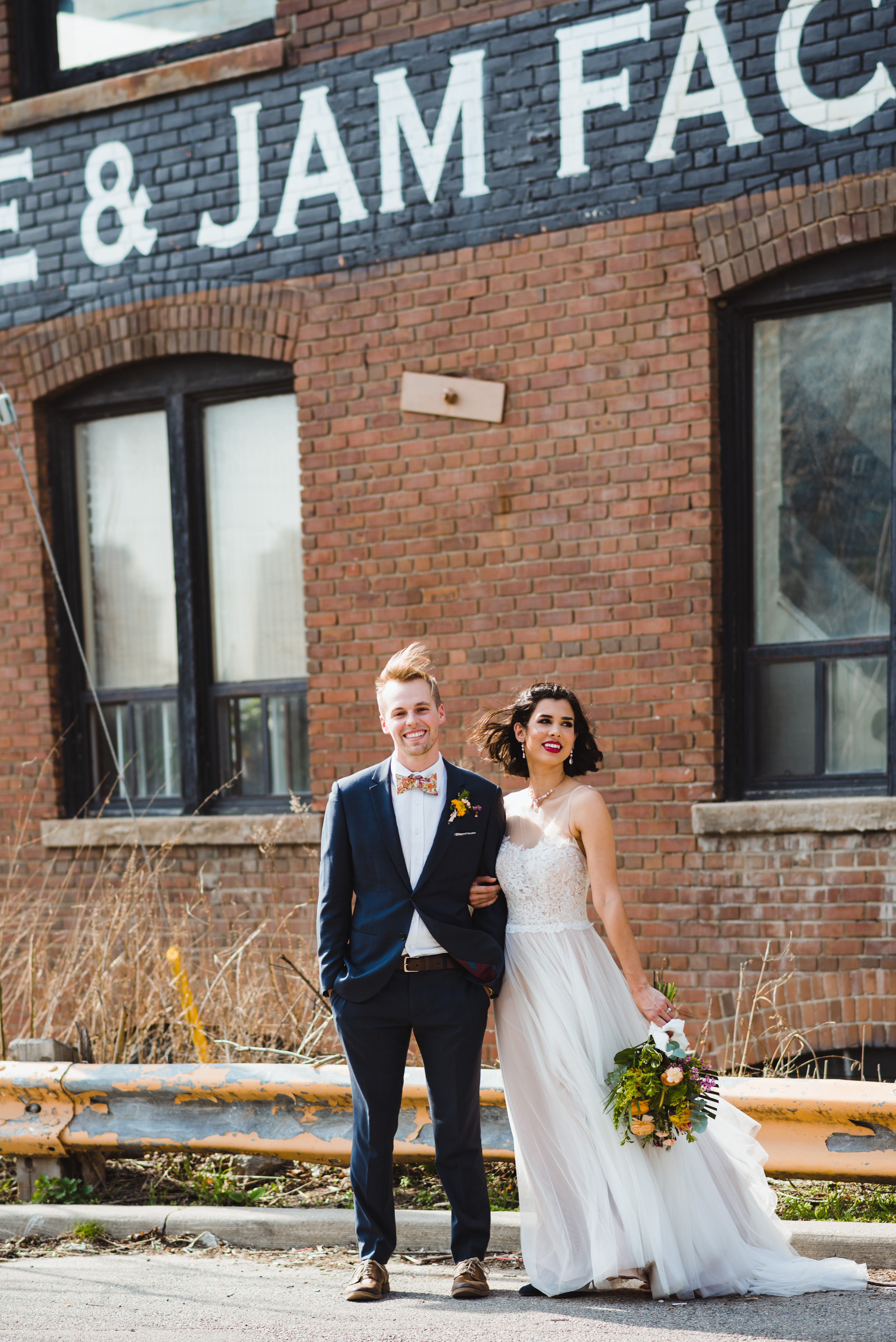 bride and groom linked arms outside the Jam Factory Toronto wedding photography