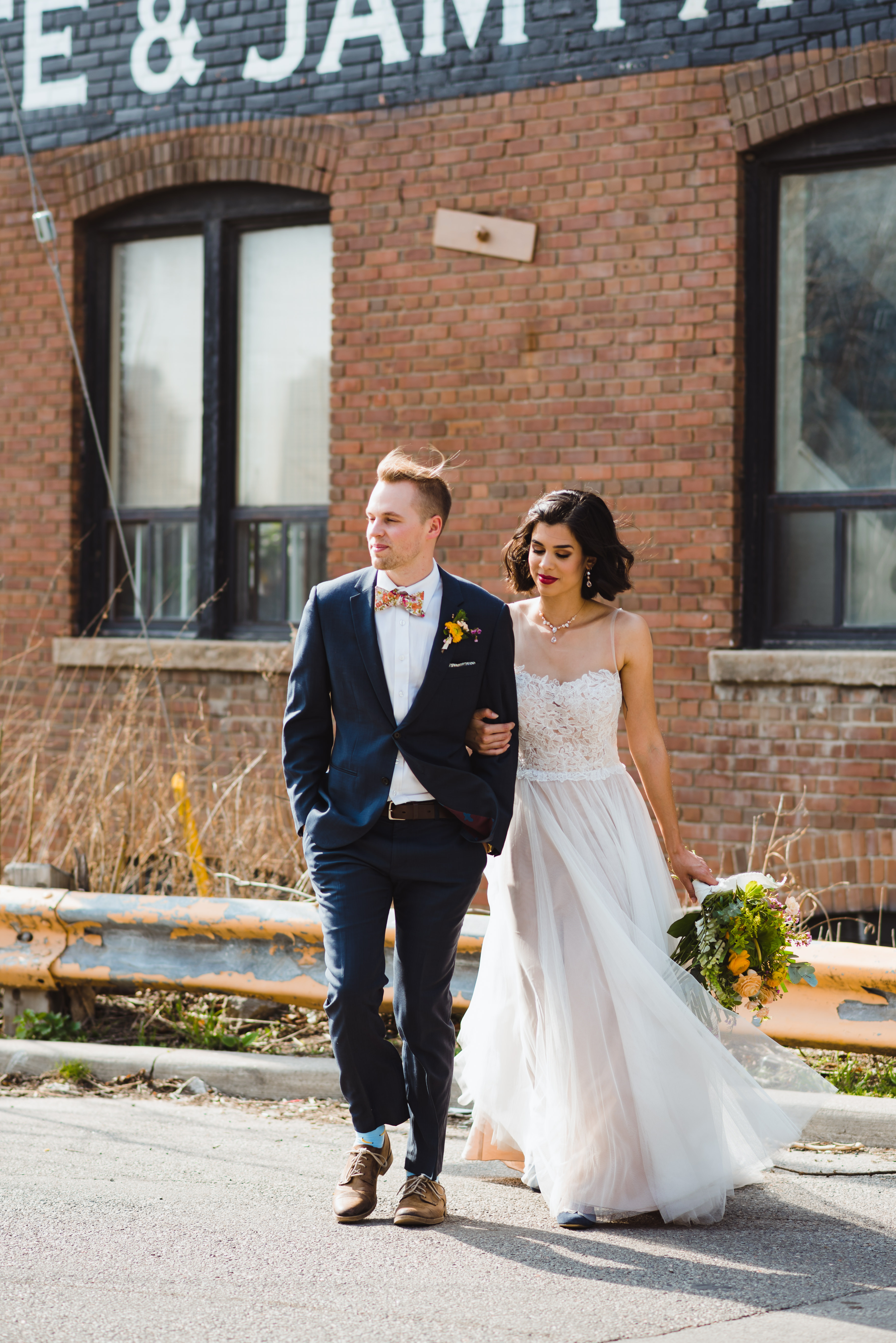 bride and groom linked arms outside the Jam Factory Toronto wedding photographer Gillian Foster