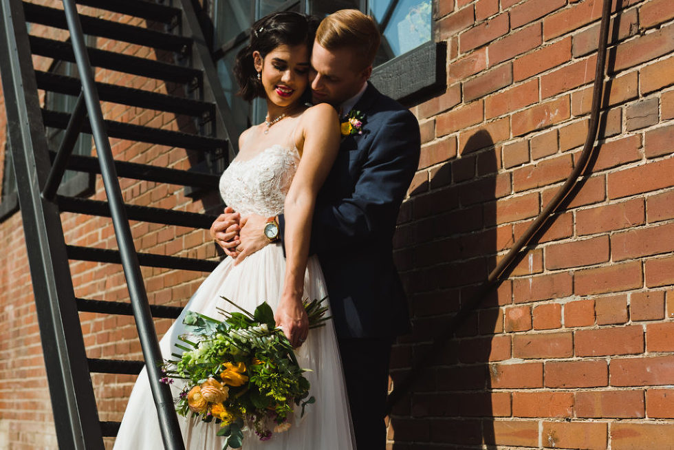 bride and groom in loving embrace on black fire escape staircase of the Jam Factory Toronto wedding photography