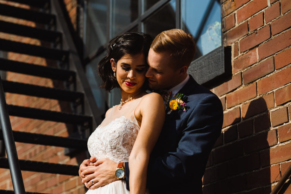 closeup of bride and groom in loving embrace on black fire escape staircase of the Jam Factory Toronto wedding photography