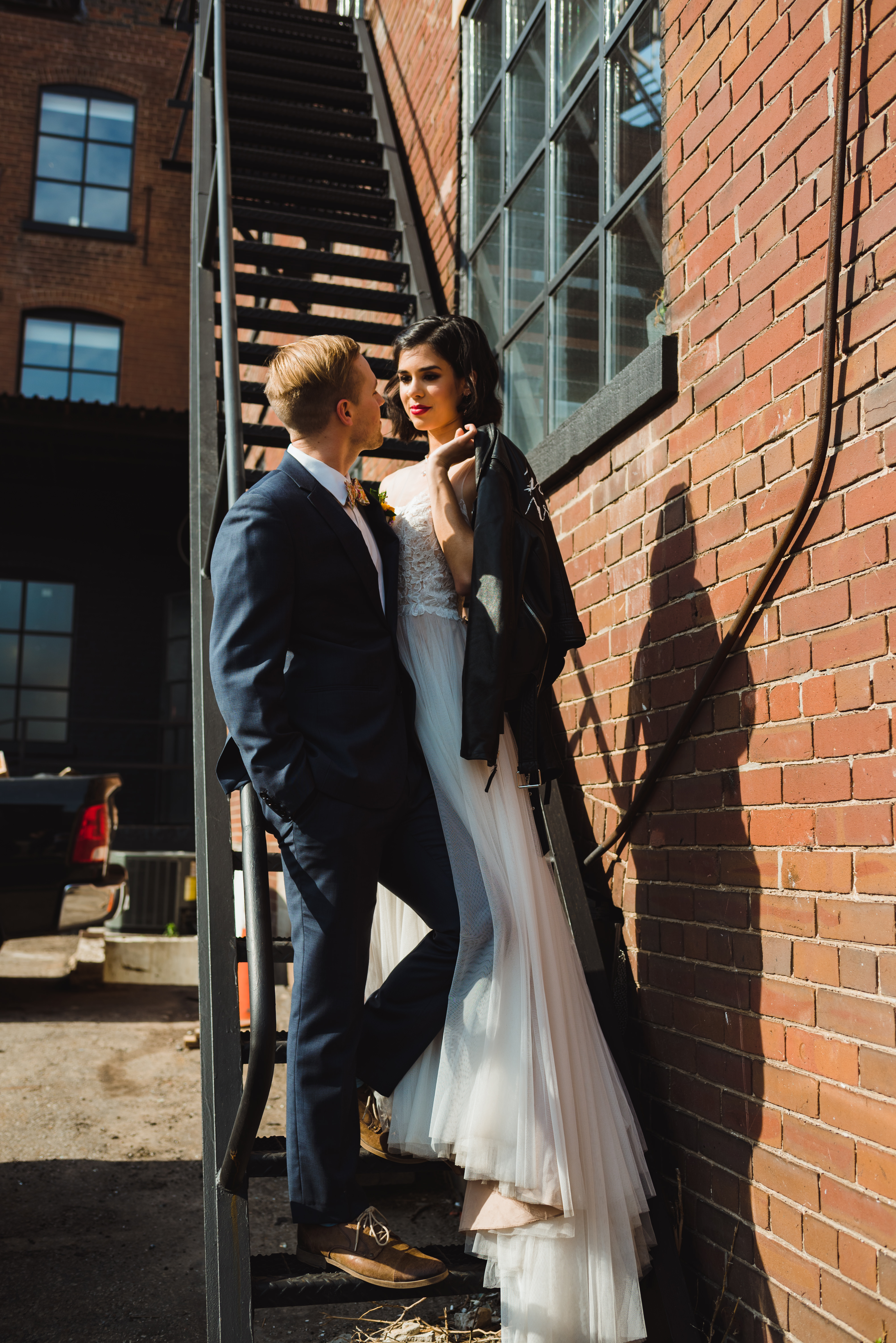 bride holding just married leather jacket over her shoulder and standing next to her groom in loving embrace on black fire escape staircase of the Jam Factory Toronto wedding photography