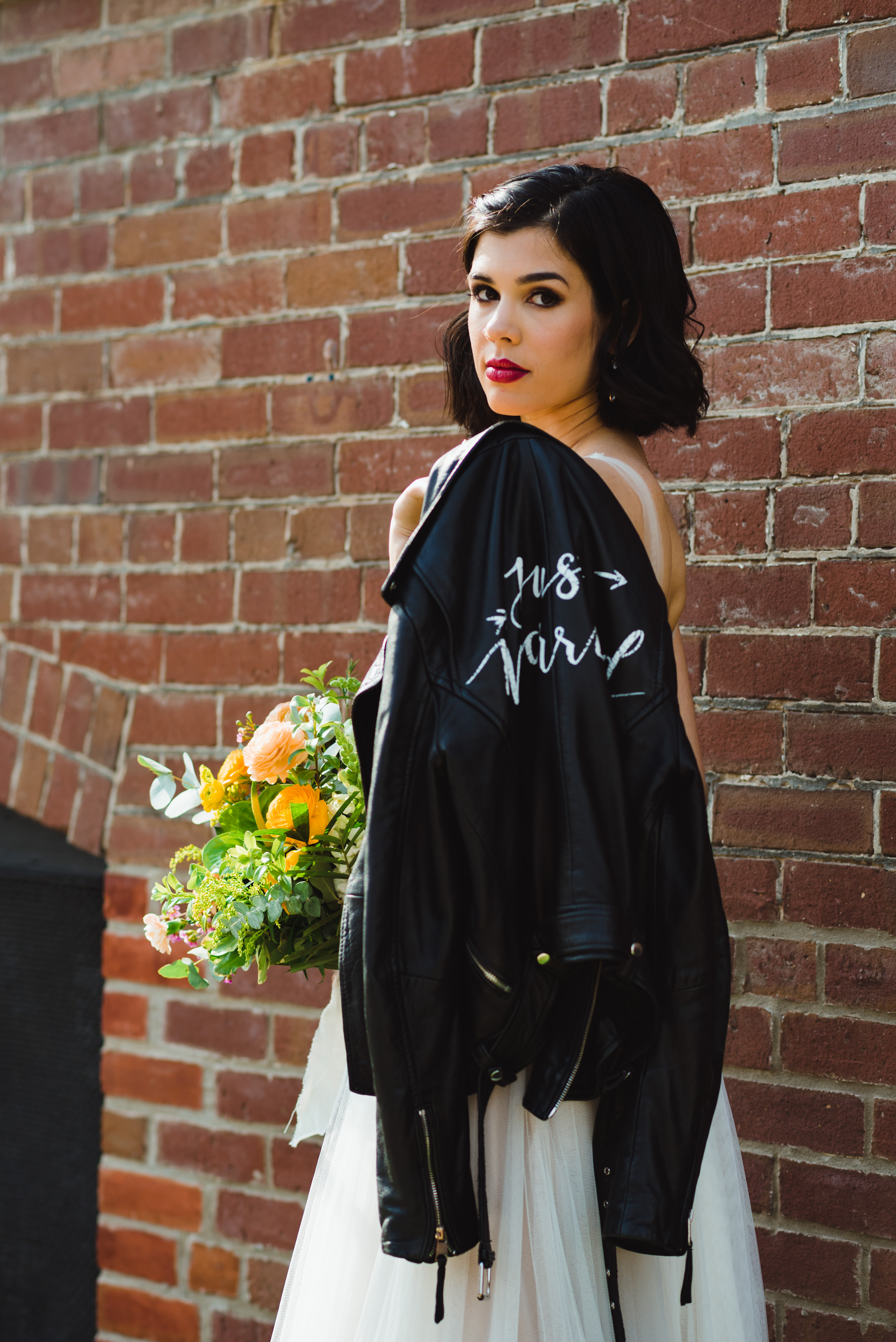 bride with just married leather jacket over her shoulder and holding bouquet standing in front of red brick wall of the Jam Factory Toronto wedding photography