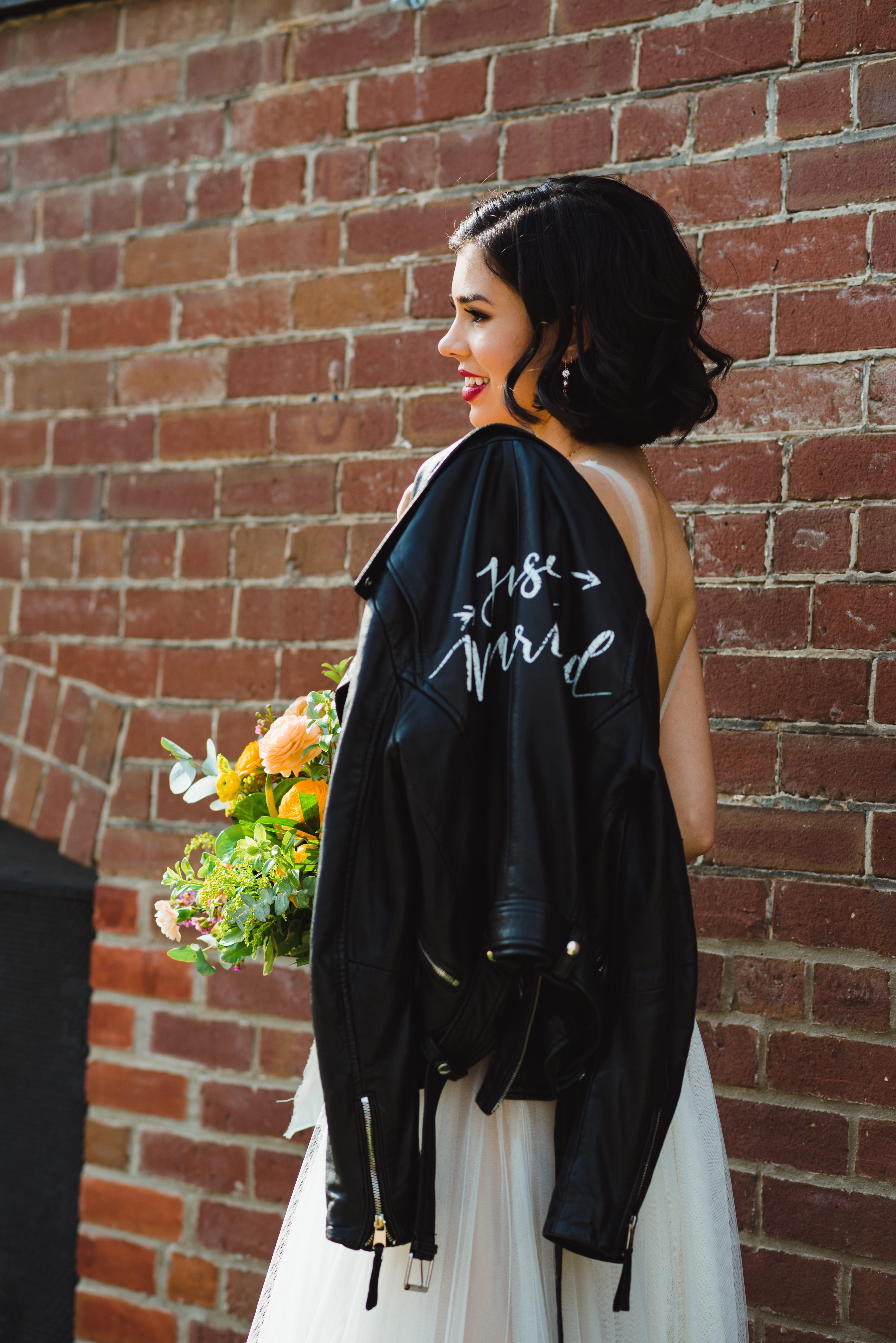 bride with just married leather jacket over her shoulder and holding bouquet standing in front of brick wall of the Jam Factory Toronto wedding photography